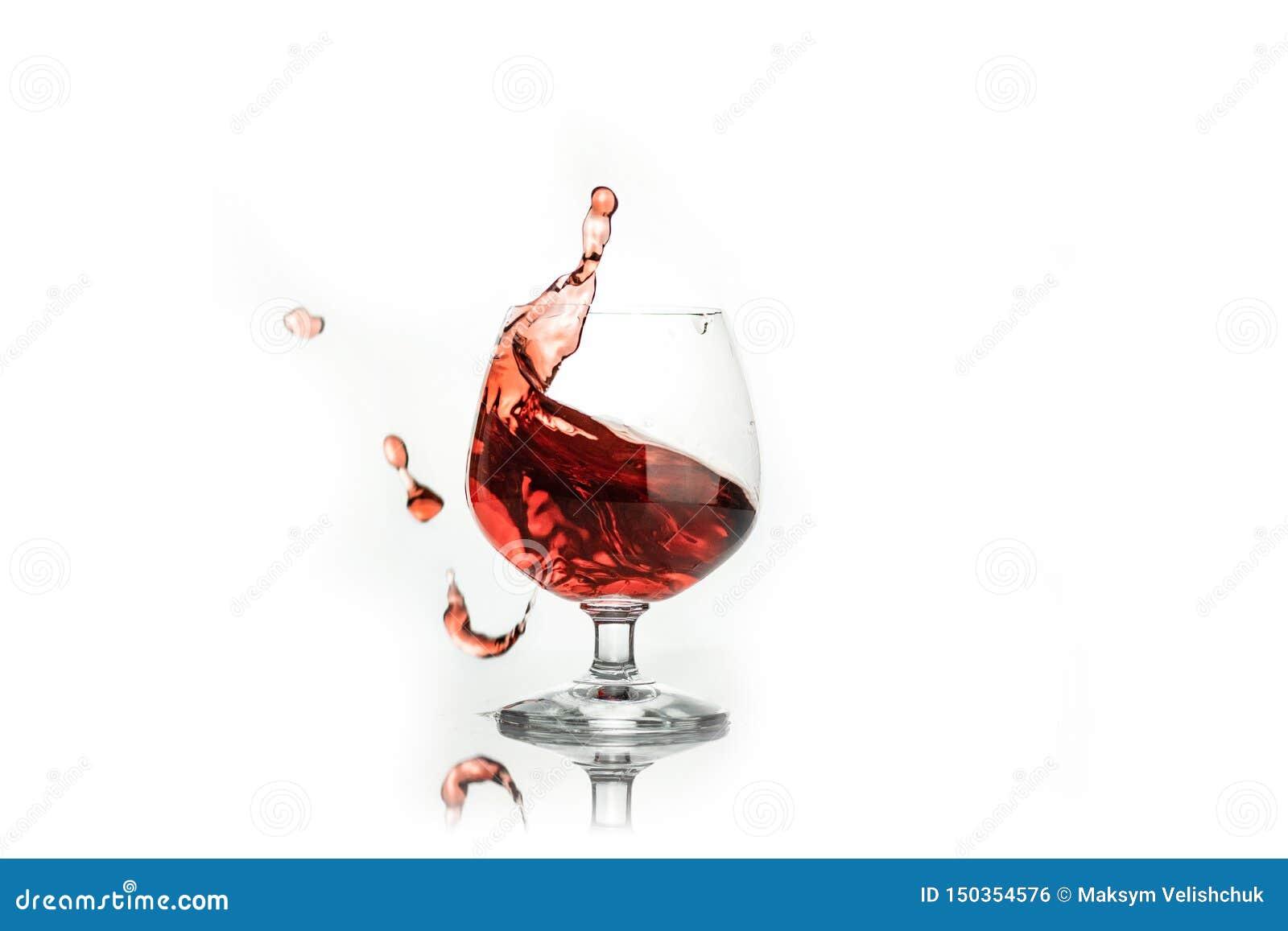 Vino rosso che spruzza da un vetro, su bianco