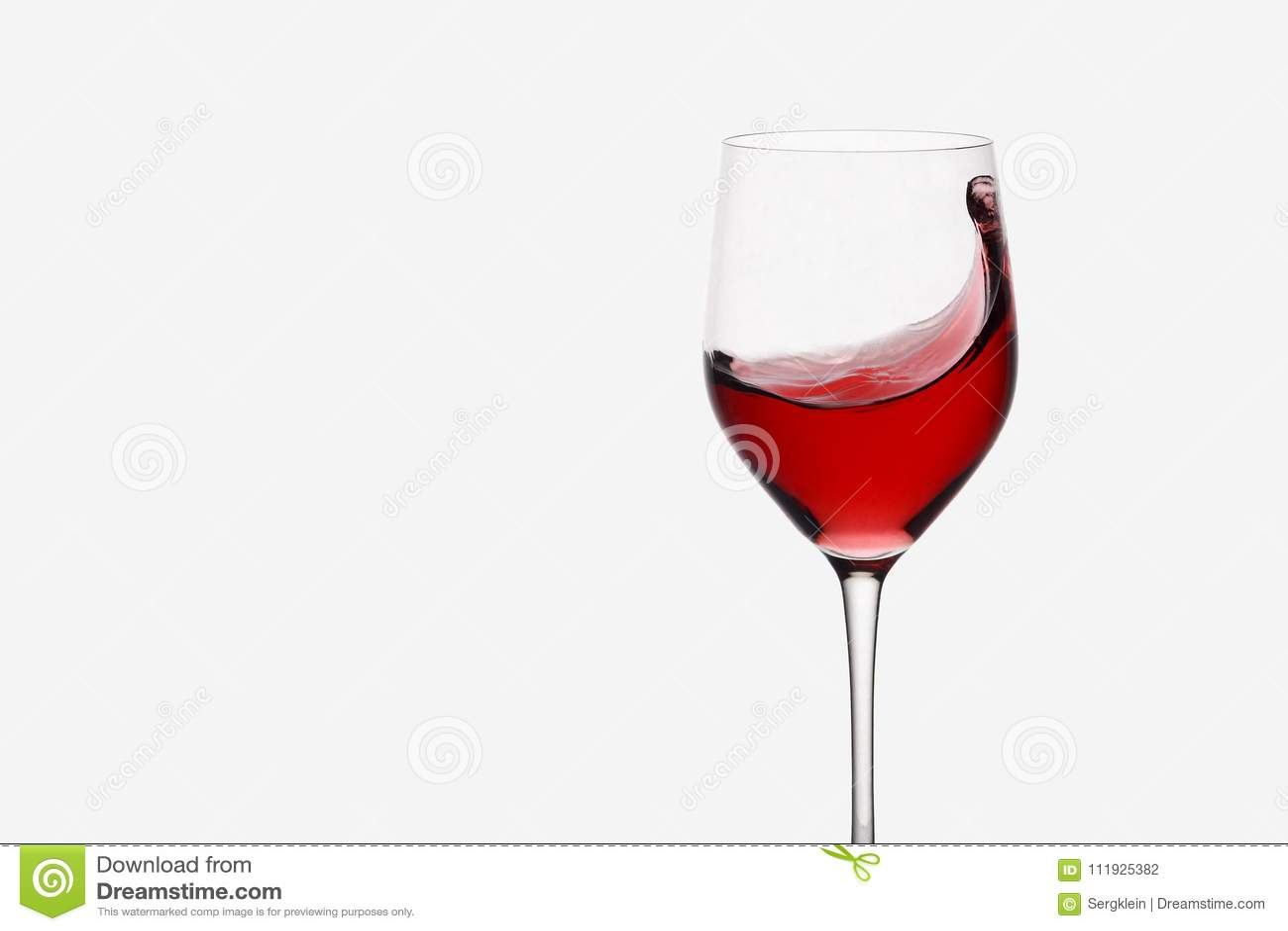 Vino rosso che turbina in un vetro di vino che sta contro il fondo leggero