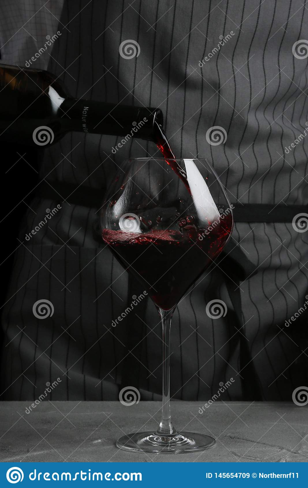 Vino rosso che versa in vetro barista sul concetto del cameriere su fondo nero