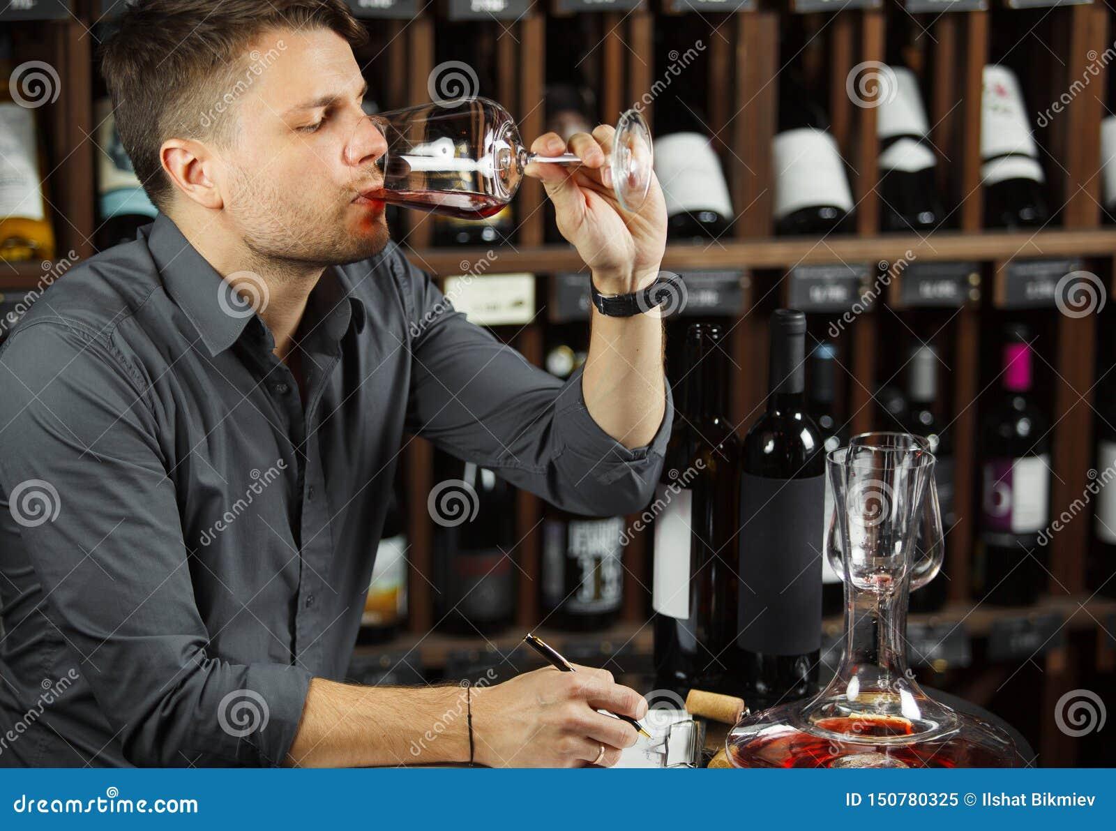 Vino tinto degustating del Sommelier bebiéndolo