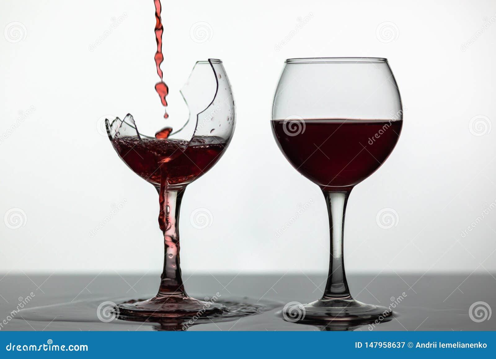 Vino tinto que vierte en la copa de vino quebrada en la superficie mojada El vino rosado Vierte