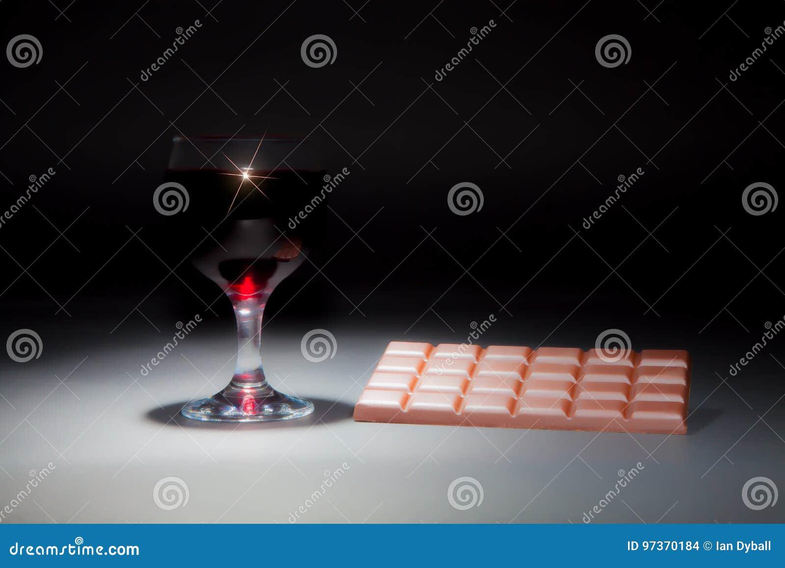 Vino y chocolate Imagen soñadora suave de un vidrio de vino rojo y