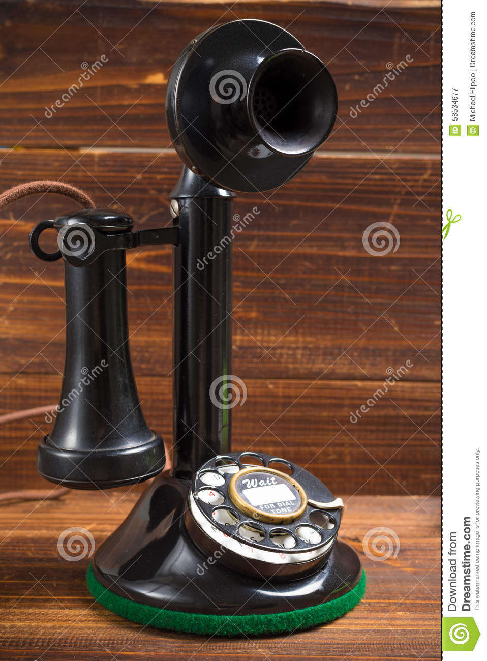 Vintage, antique candlestick telephone with dial on wood background