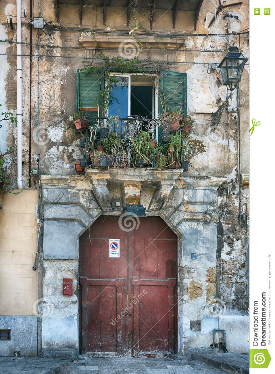 Vintage balcony with different flowers, cracked plaster and wooden doors, Mediterranean style