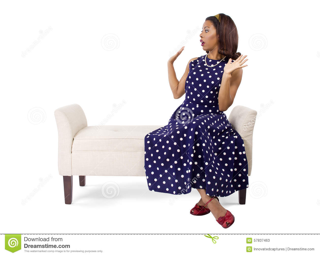 8376937b42 Woman wearing a blue polka dot dress on a traditional chaise furniture. The  model is isolated on a white background.