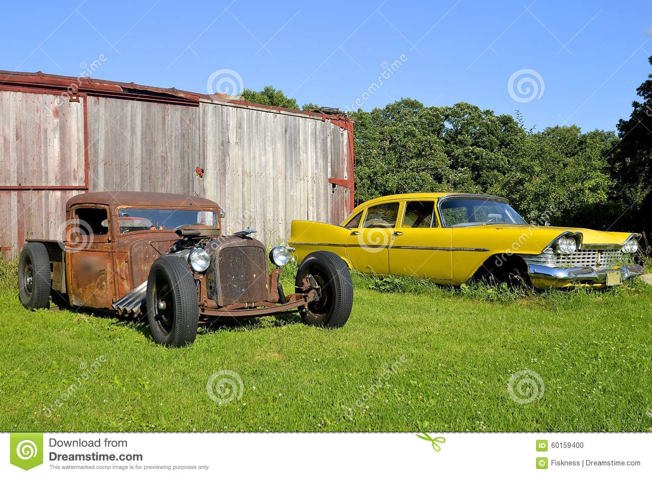 Vintage cars alongside a railroad box car