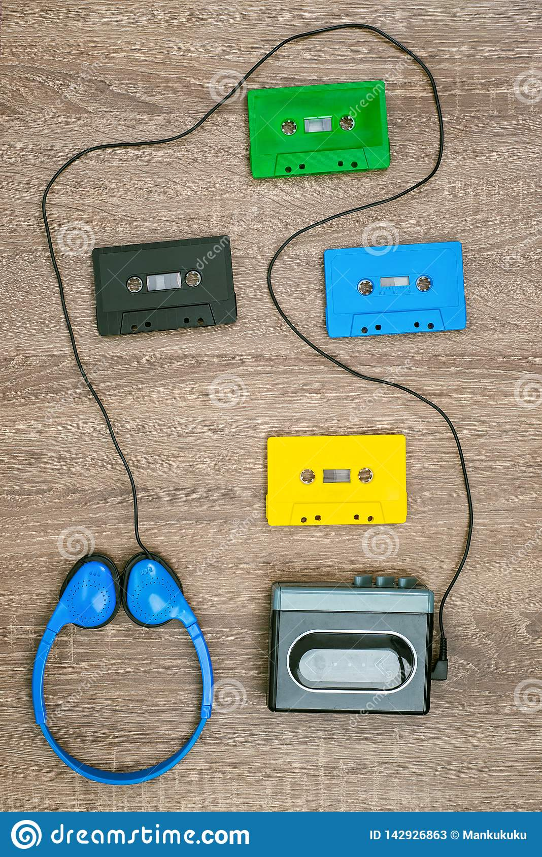 Vintage cassette player, cassetes and headphones on the wooden background.