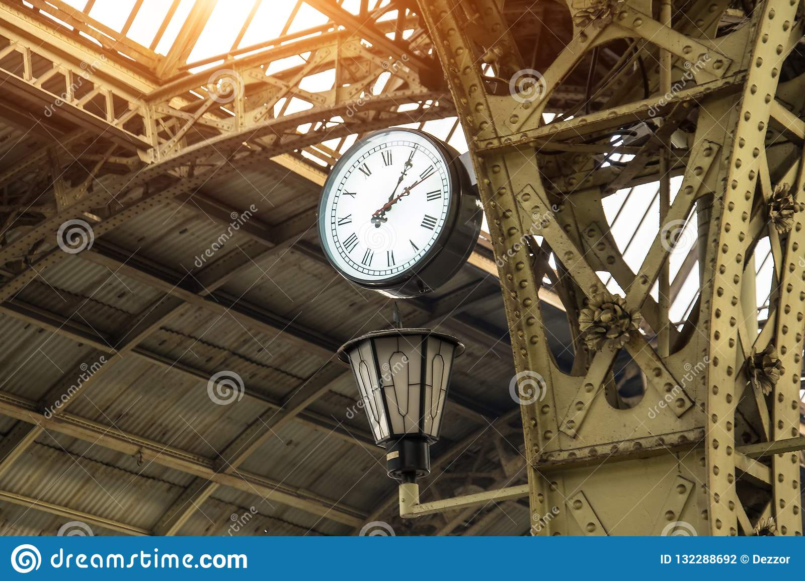Vintage clock and lantern on train station with building roof