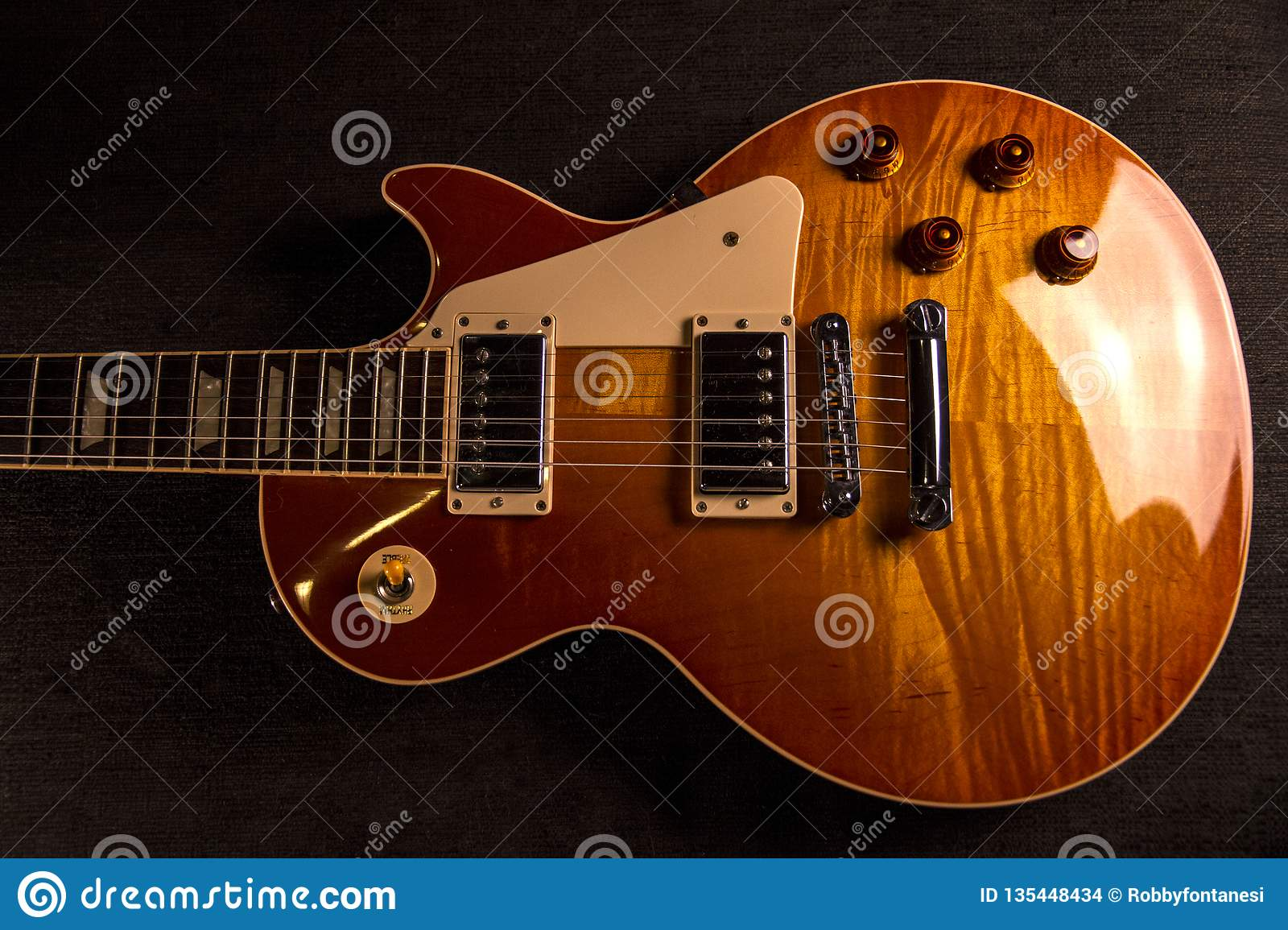 Vintage electric guitar with the perfect paint of a bright cherry color with almost metallic reflections