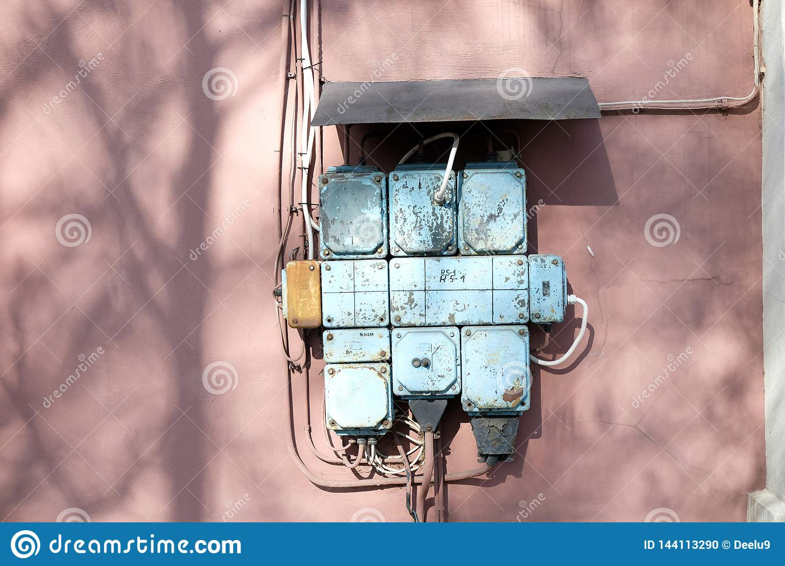 A vintage fuse box on a pink wall