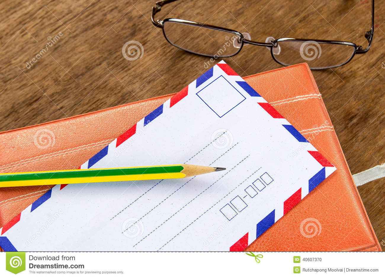 Vintage envelope, pencils, notebook and glasses on a wood floor