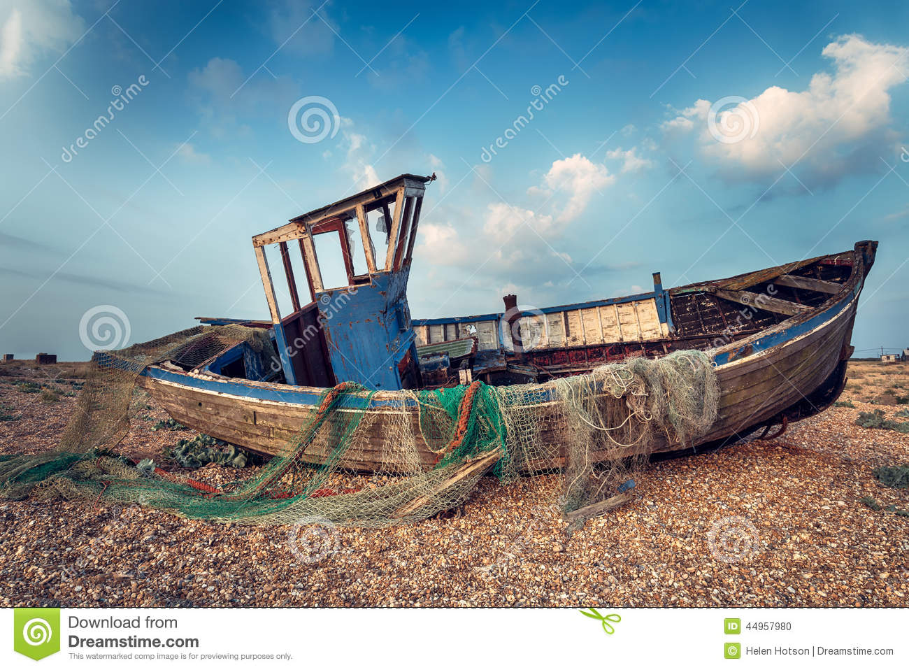 Old wooden fishing boat washed up on a shingle beach.