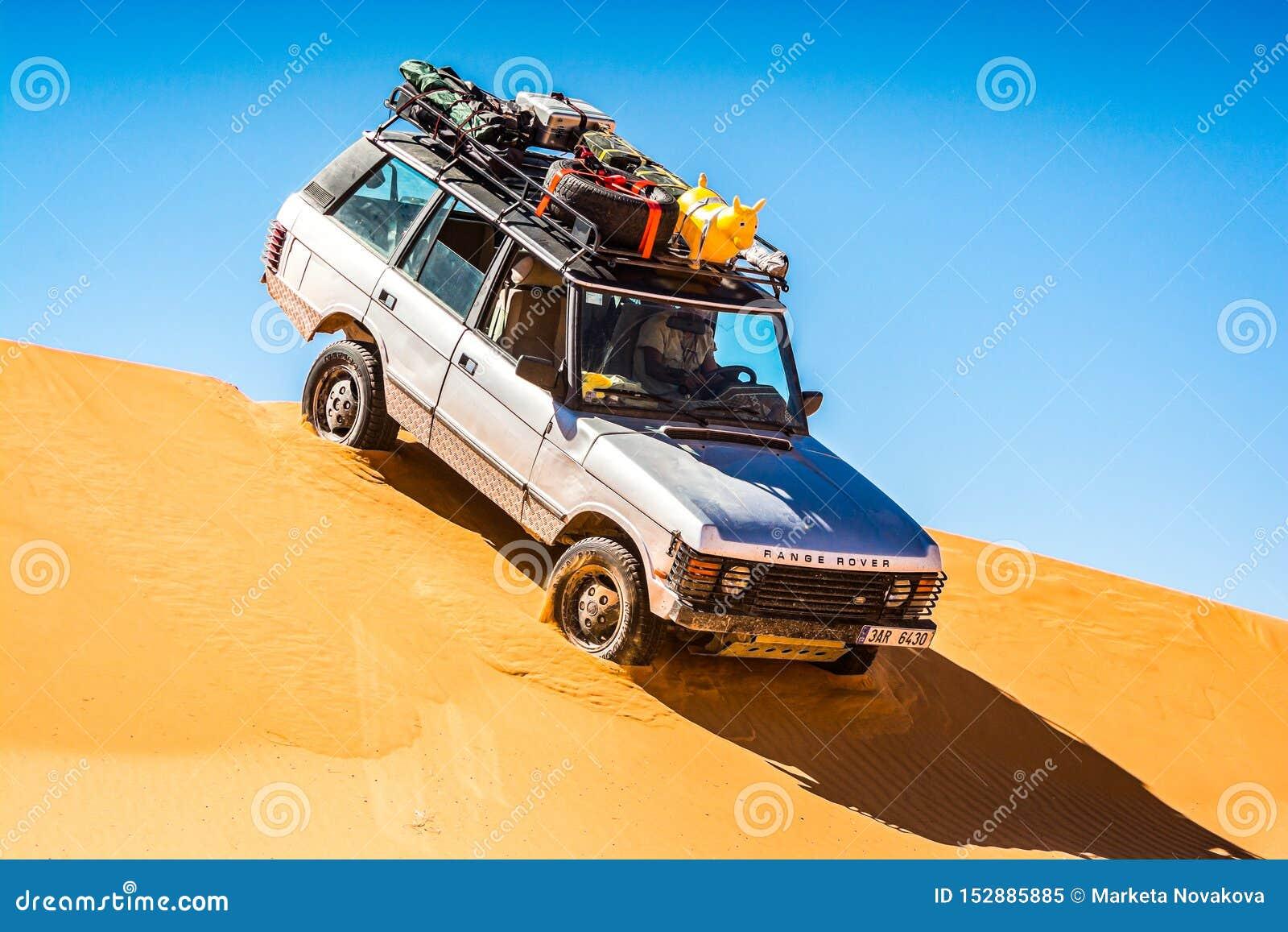 Vintage fora da condução de carro da estrada da duna de areia em Merzouga, ERG Chebbi em Marrocos