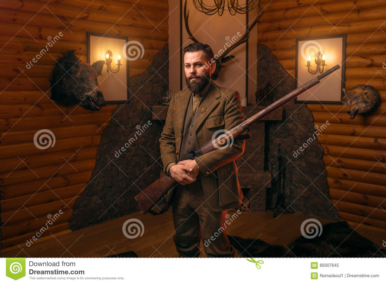 8d21fa83518f4 Hunter gentleman in traditional hunting clothing with old gun against  fireplace. Stuffed wild animals, bear skin and other trophies on background.