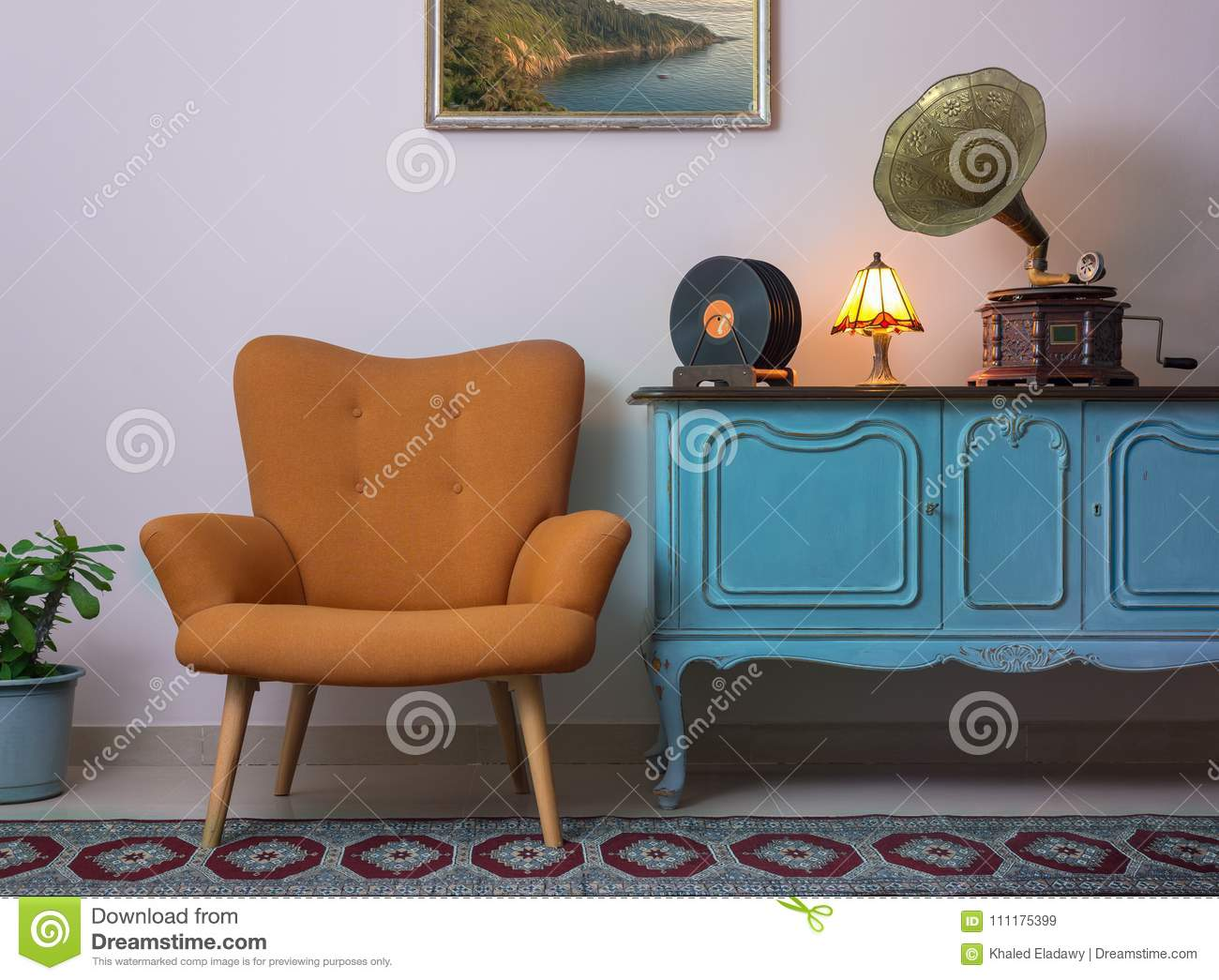 Vintage interior of retro orange armchair, vintage wooden light blue sideboard, old phonograph gramophone and vinyl records