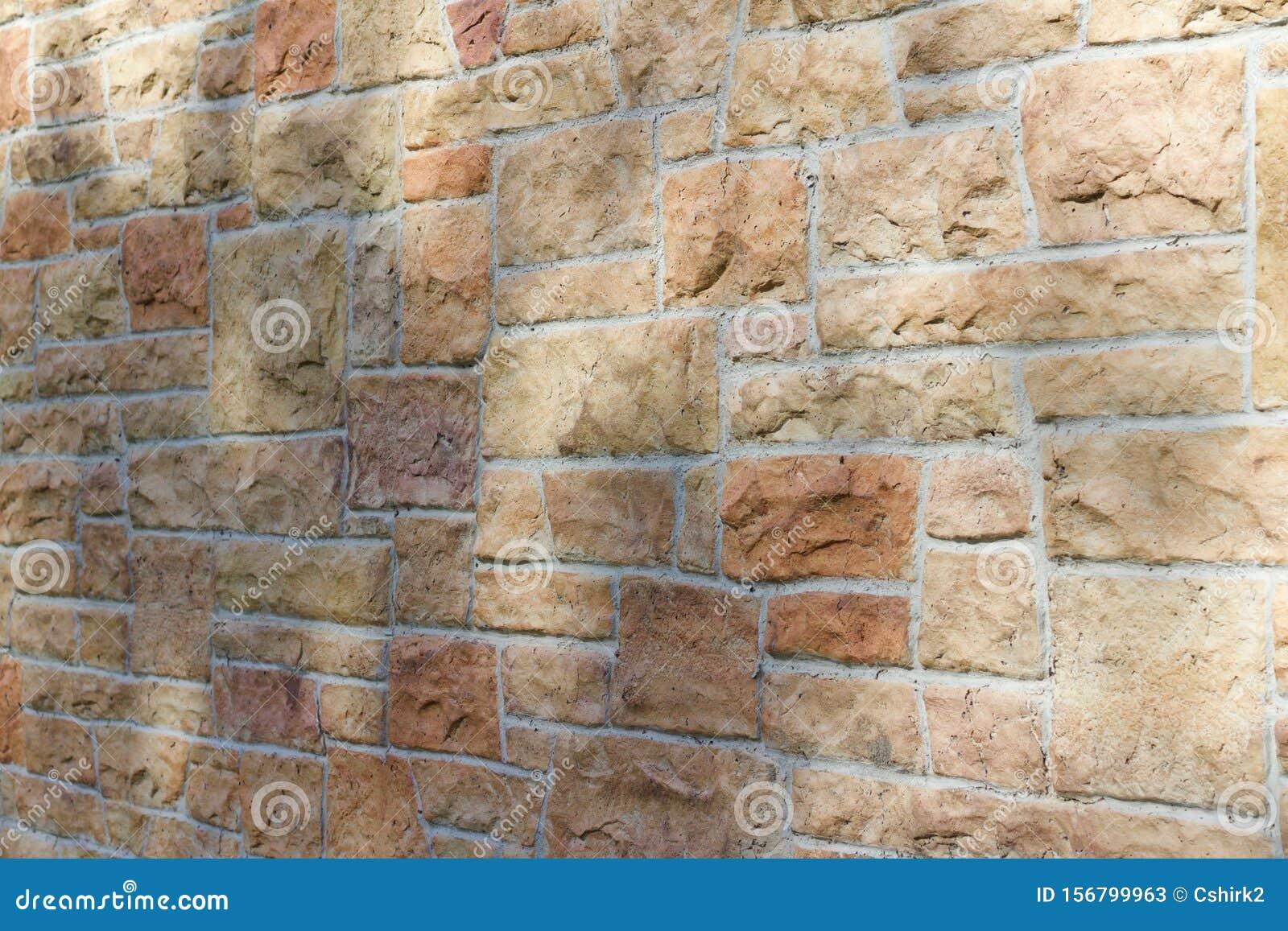 Vintage kasota limestone brick wall texture in colors of orange and pink beige