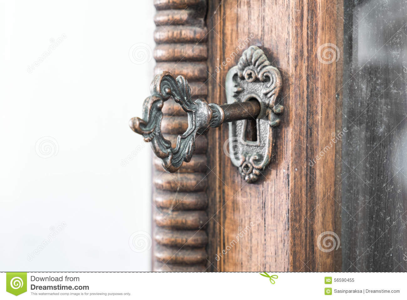 Vintage keyhole with key on wooden cabinet