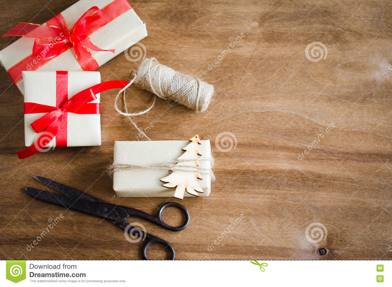 Vintage kraft boxes with gifts, tied with red ribbons and jute with wooden christmas tree on rustic background.