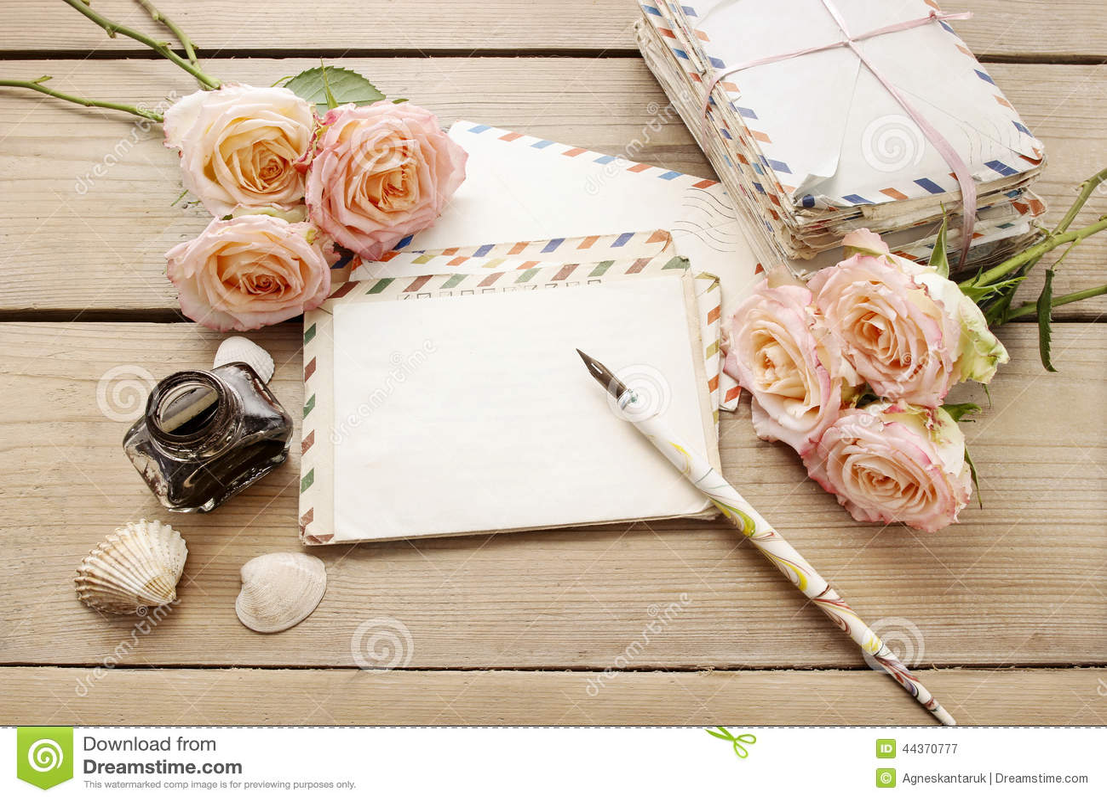 Старинные письма, розы и бутылка чернил на деревянном столе .