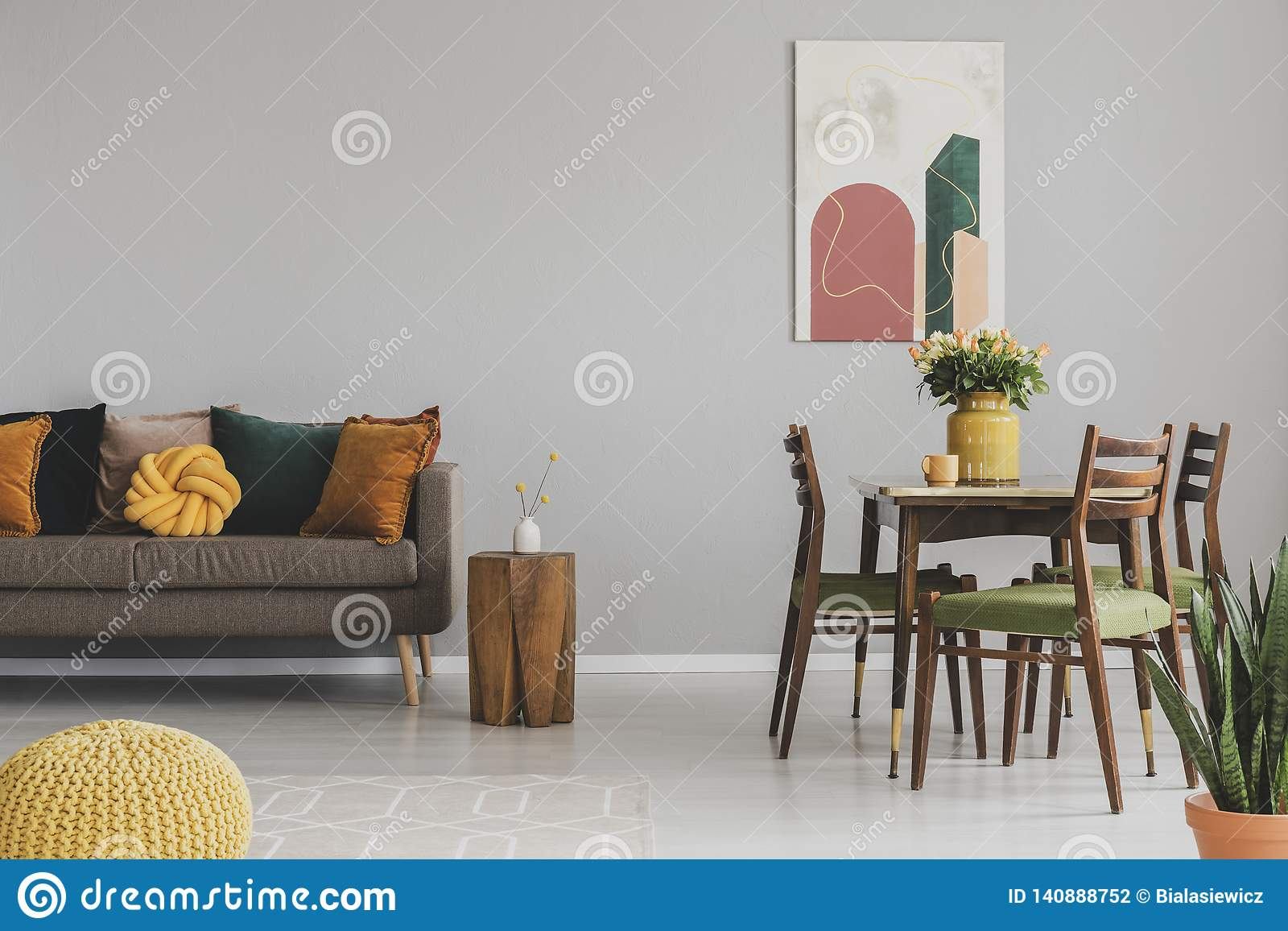 Vintage living and dining room interior with retro table with chairs and comfortable sofa with pillows