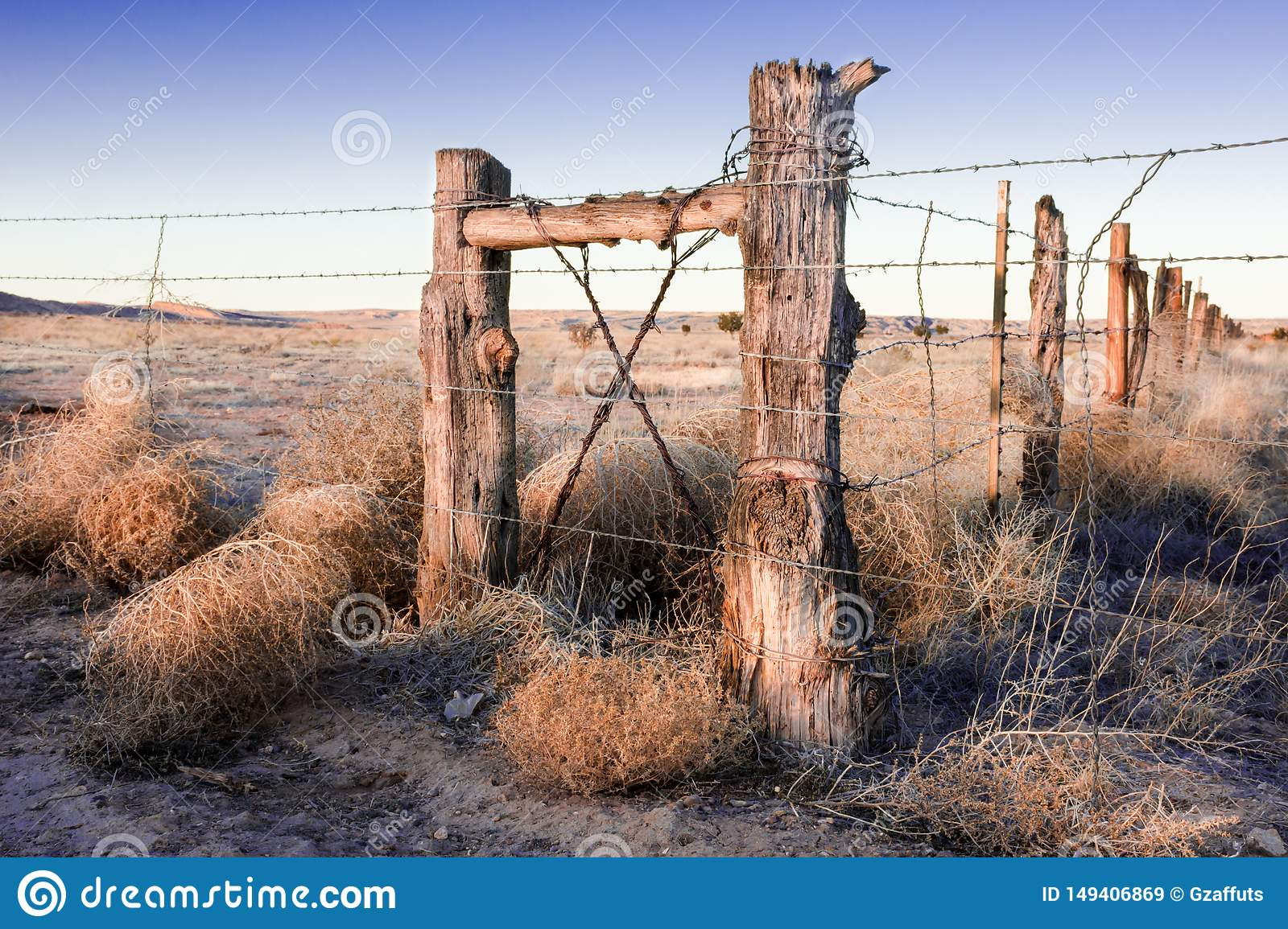 Vintage log fence on old Route 66 in New Mexico at sunset.
