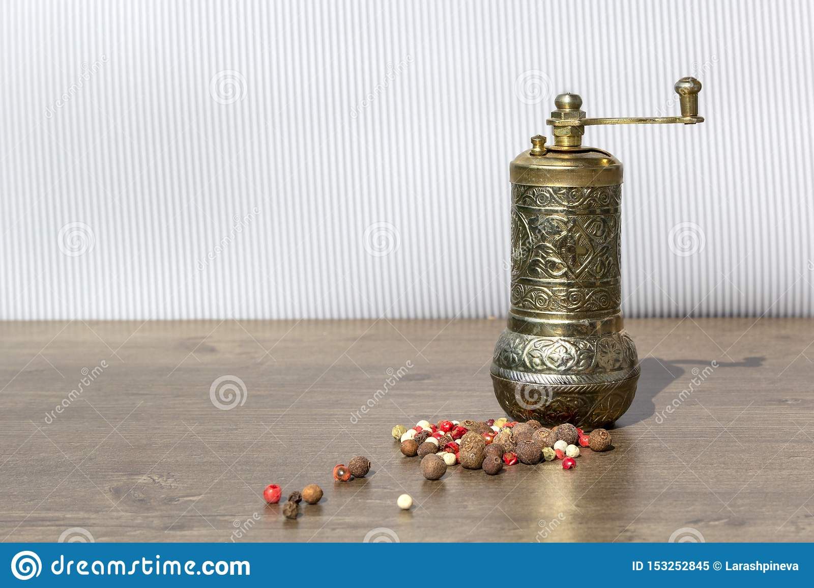 Vintage mill for pepper with black peppercorns and allspice on wooden table. Kitchen appliances for grinding spices and salt