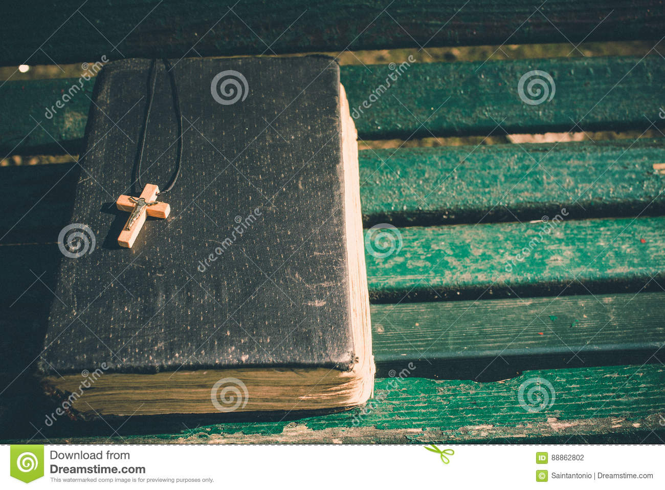 Vintage old holy bible book, grunge textured cover with wooden christian cross. Retro styled image on wood background.