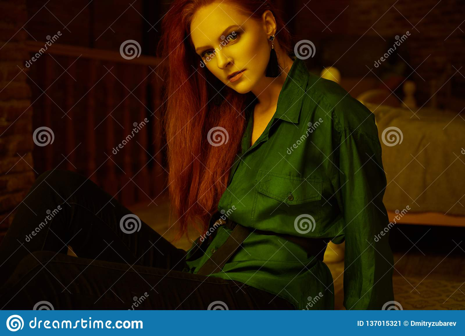 53c951a60e000 Ginger lady posing in loft apartment in Tbilisi. She wears green shirt and black  jeans. Her hair is curly. Flat has big window. Walls are of red bricks.