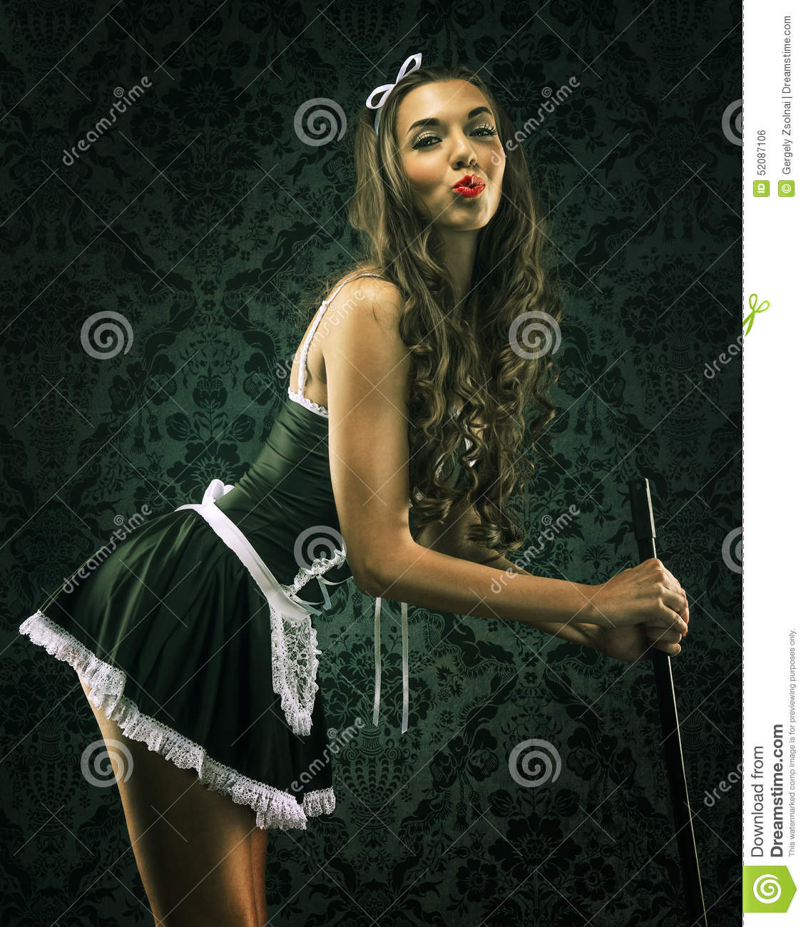 Vintage pin up maid's uniform, holding a broom .