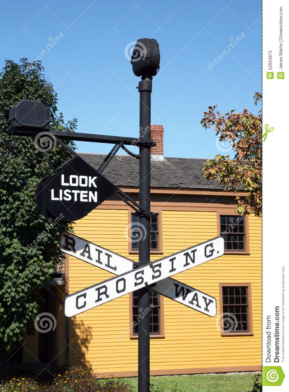 Vintage Railroad Crossing Sign With Building In Background