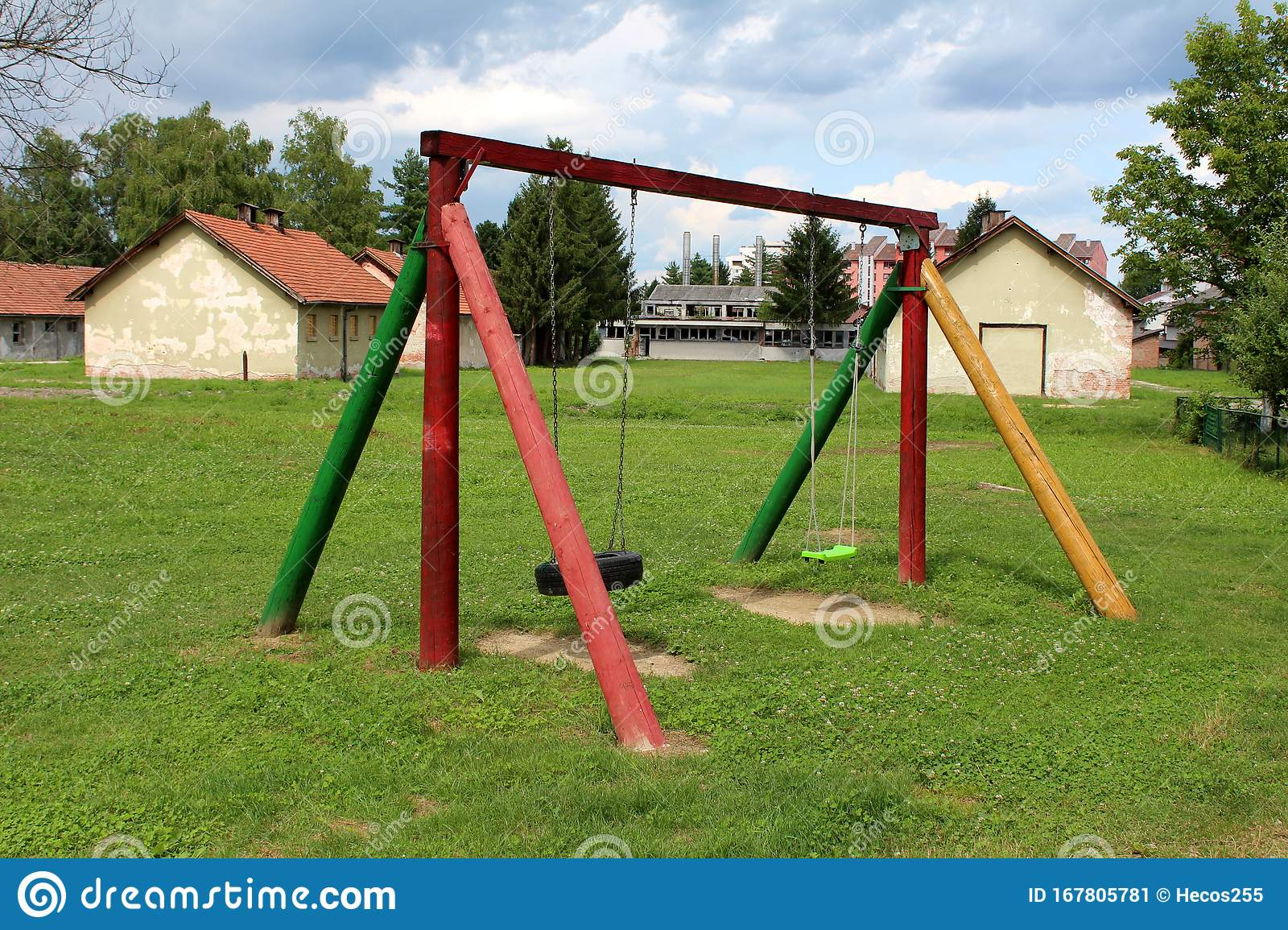 Vintage Retro Colorful Wooden Outdoor Public Playground Equipment In Shape Of Swing In Front Of Abandoned Military Complex Stock Image Image Of Seats Military 167805781