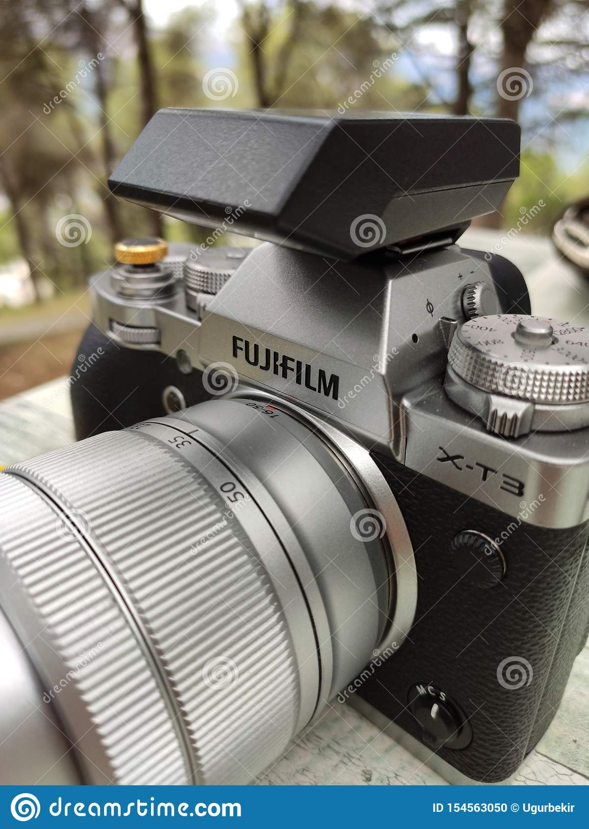 Vintage silver and black Fujifilm camera with brown leather strap on wooden table. Copy space for text