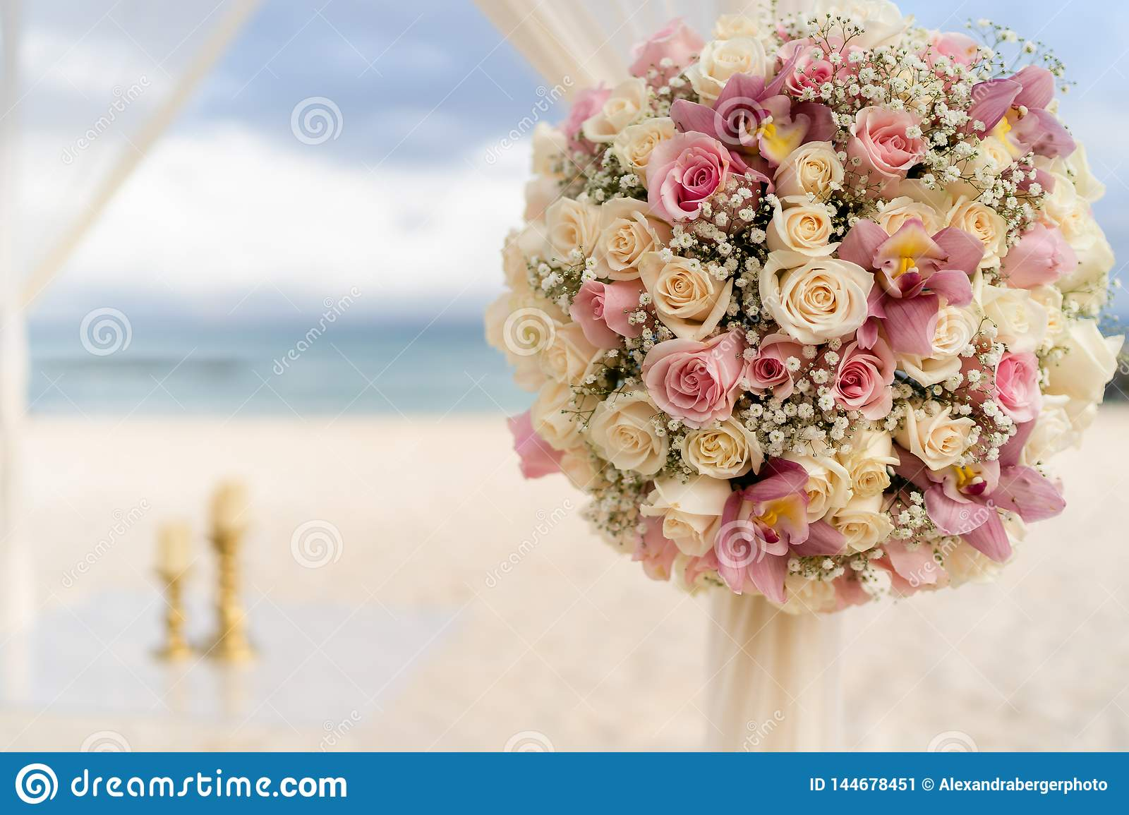 Romantic decoration with flowers of a beach wedding on the beach with sea in the background