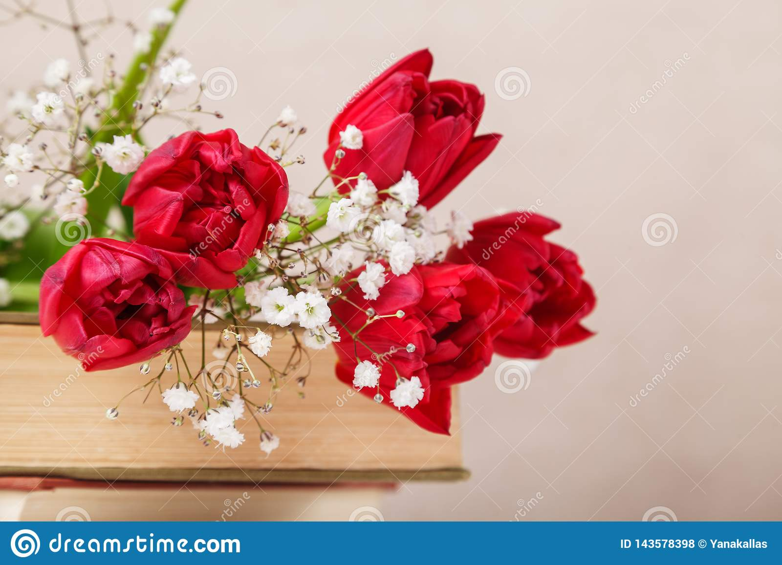 Vintage still Life with a spring red tulips and a books on a beige background. Mother`s day, women`s day concept