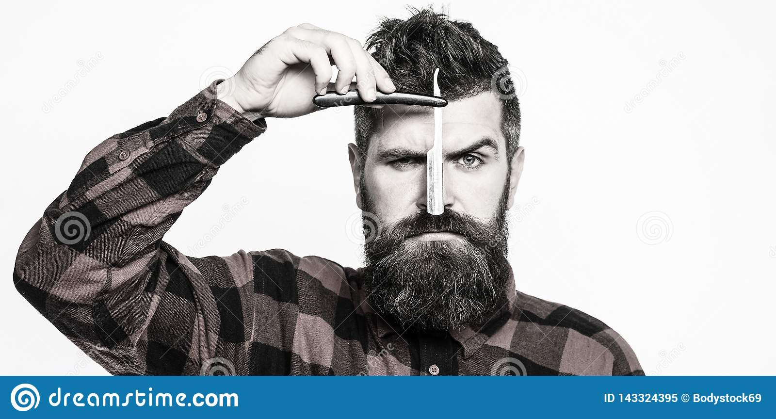 Vintage straight razor. Barbershop service concept. Handsome bearded hairdresser is holding a straight razor while