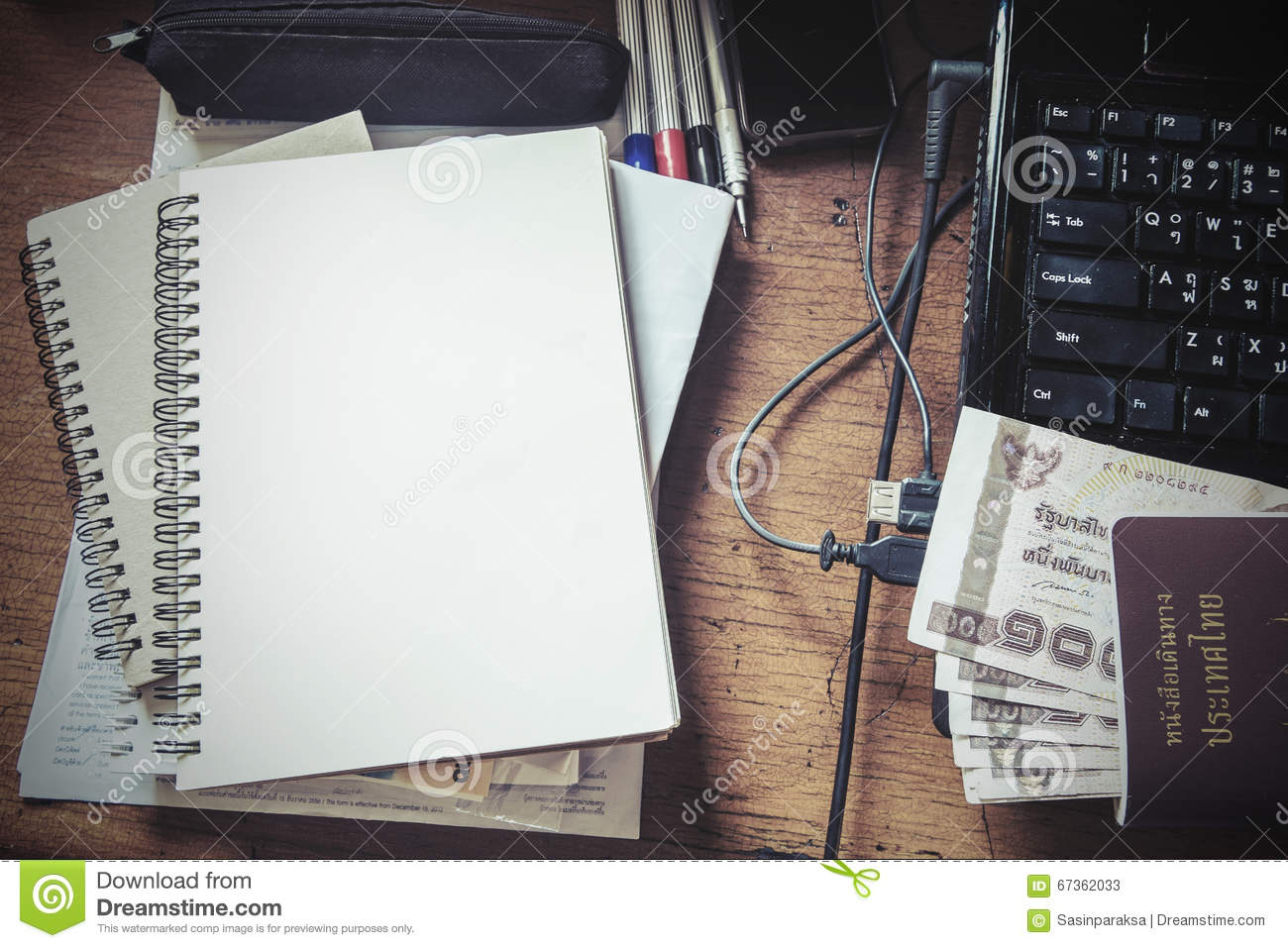 vintage tone messy working table with blank notebook passport