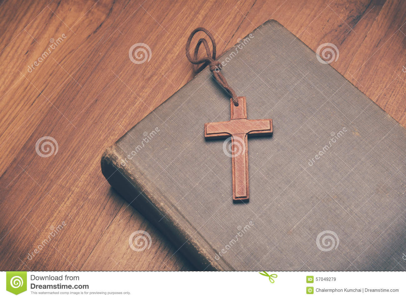 Vintage tone of wooden Christian cross necklace on holy Bible