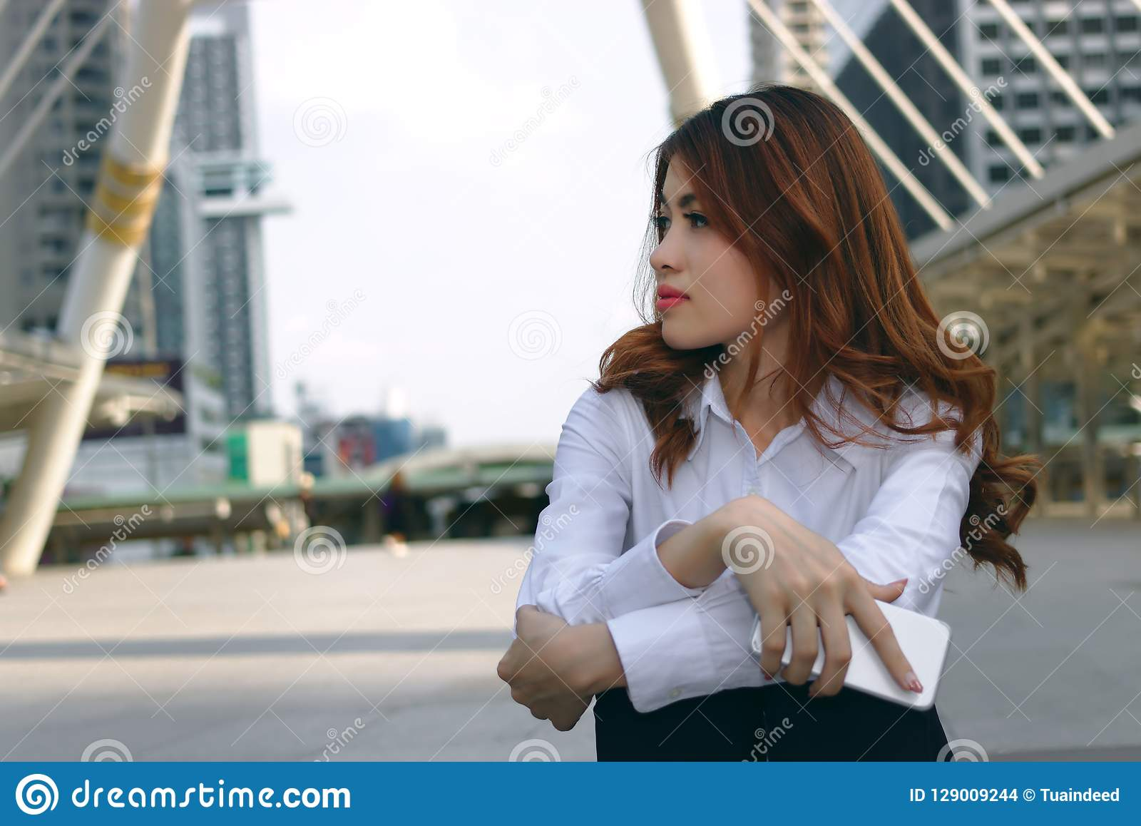 Vintage toned image of attractive young Asian business woman thinking and dreaming about something at city background.