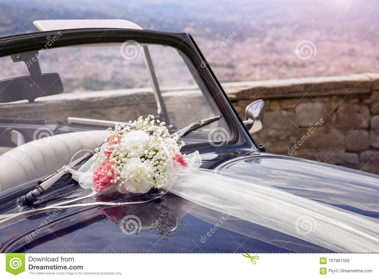 Vintage wedding car with bouquet of flowers on bonnet