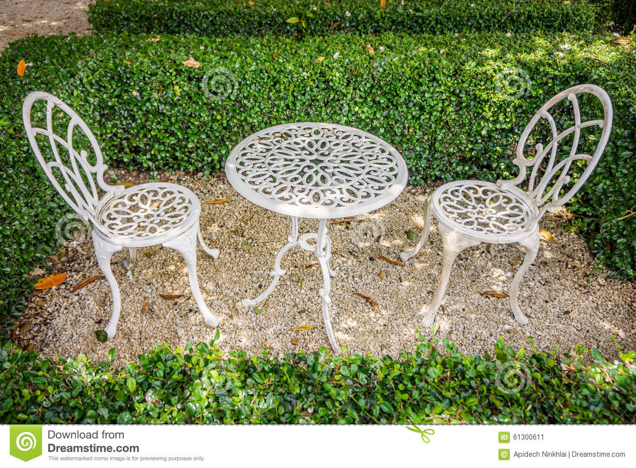 Vintage white metal table and chairs in garden stock photo for Metal garden table and chairs