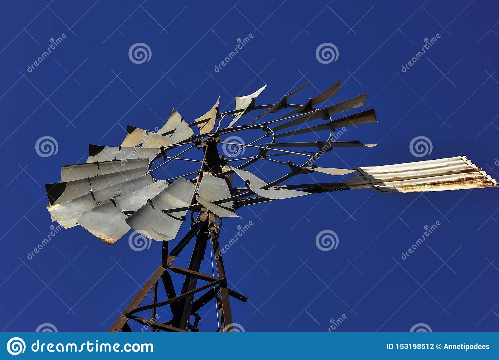 Vintage windmill, looking up into a bright blue sky, stationary capture outback Australia.