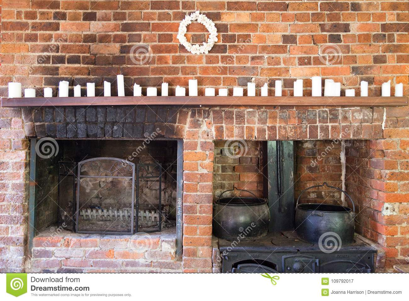 Old Fashioned Vintage Wood Burning Kitchen Stove In The Home With Black  Traditional Cauldron And Rustic Brick Fireplace With Candles On A Wooden  Mantle, ...