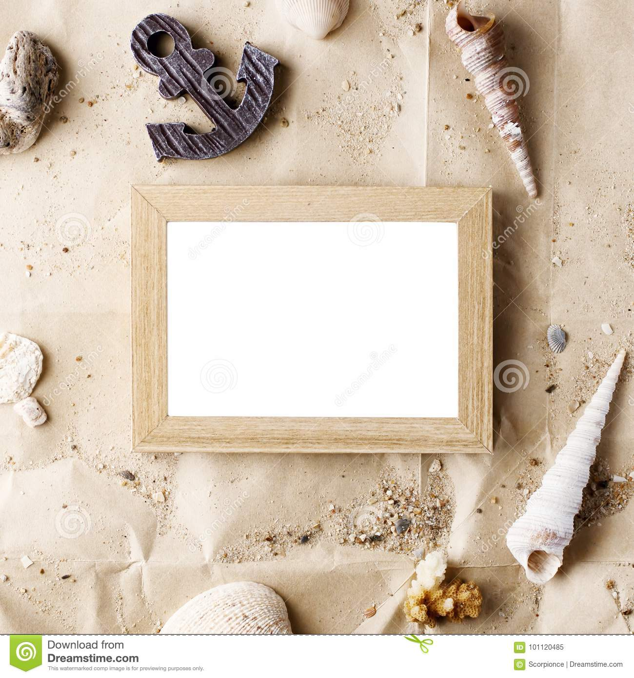 Vintage wooden photo frame on craft paper with sand and sea shells mock up