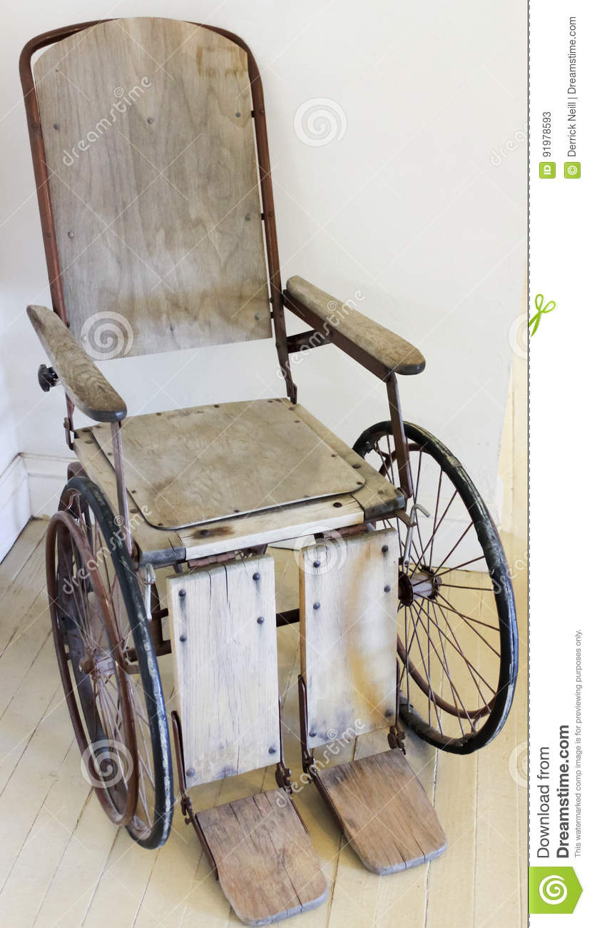 A vintage wooden rolling chair or wheelchair stock image