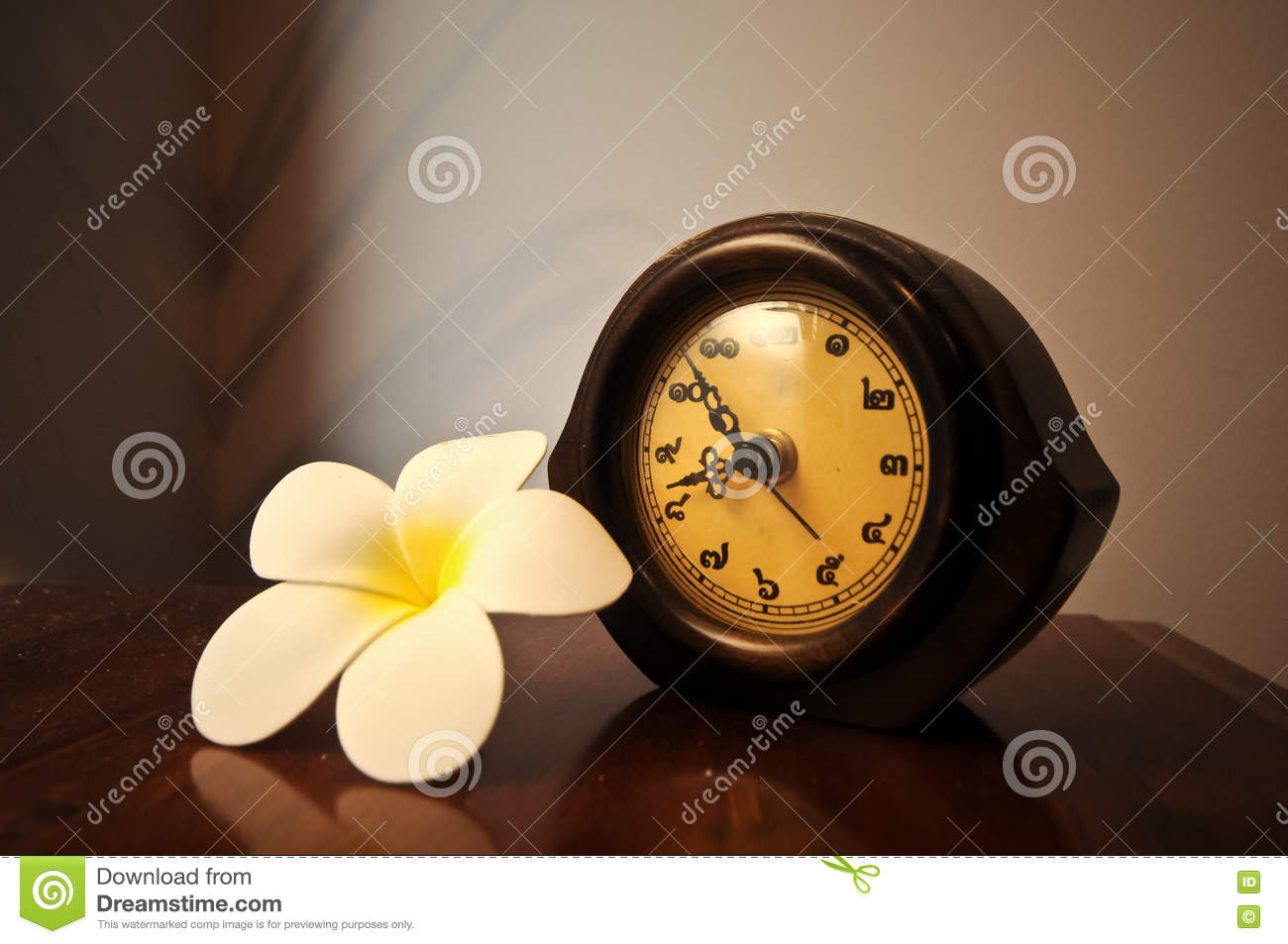 Vintage Wooden Thai Desk Clock On A Table With Plumeria Flower Stock