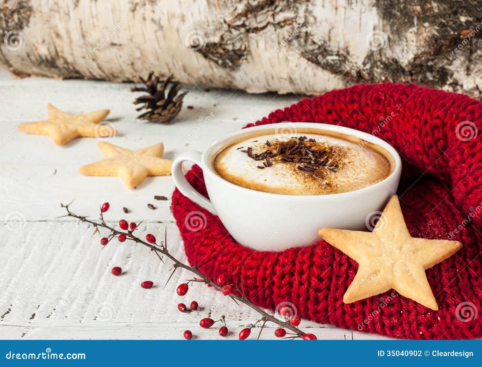 Vintercappuccinokaffe i den vita koppen med julkakor