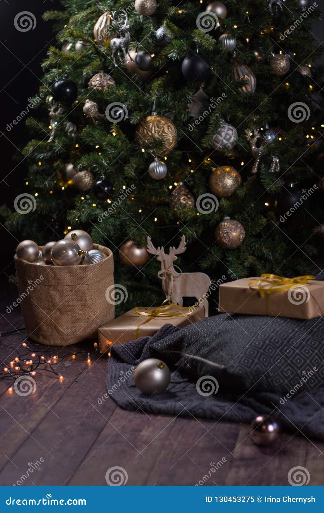 Vinterdekor: Julgran, girland, bollar, gåvor och hemtrevliga randiga och gråa pläd med kuddar