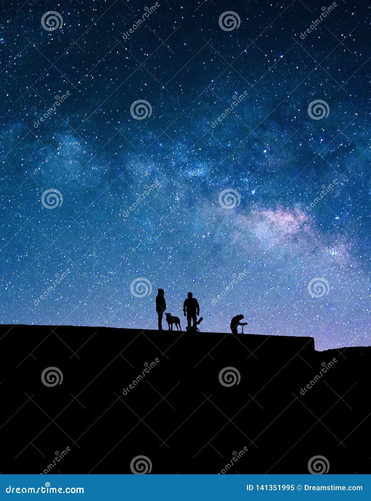 Vintergatan och konturer av folk