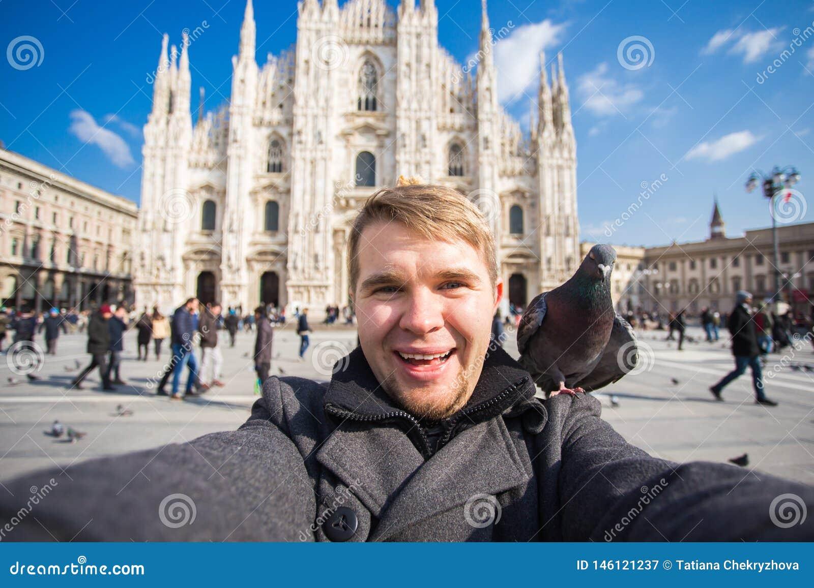 Vinterlopp, semestrar och fågelbegrepp - ung rolig man som tar selfie med duvor nära Milan Cathedral Duomo di