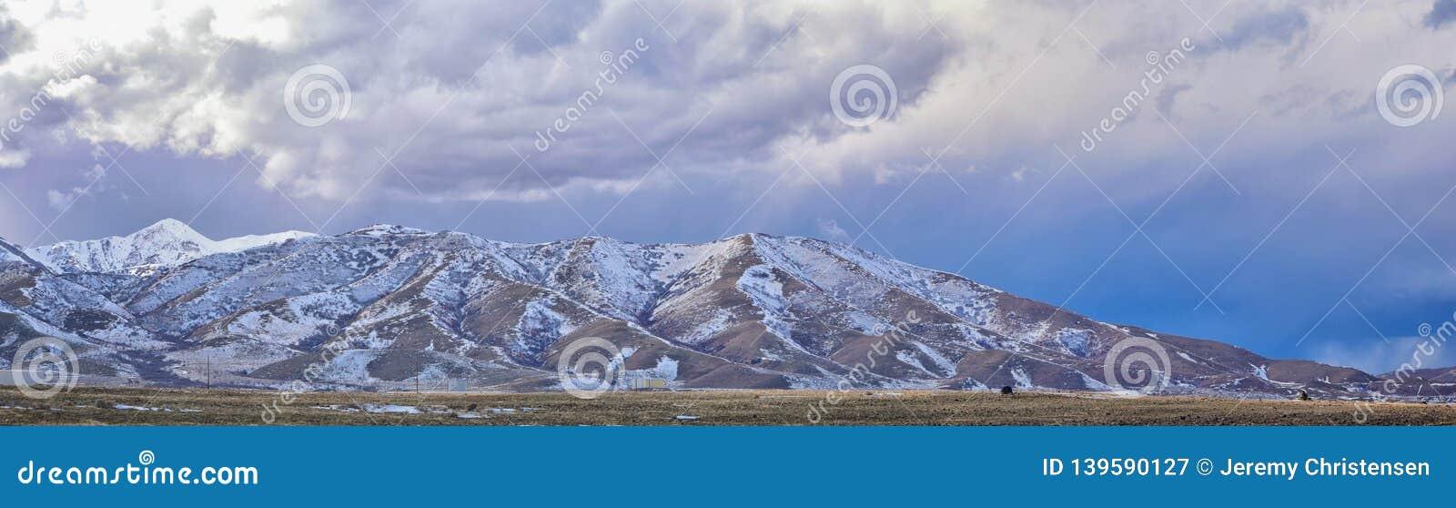 Vinterpanorama av korkad Oquirrh bergskedjasnö, som inkluderar den Bingham Canyon Mine eller Kennecott kopparminen, som det rykta